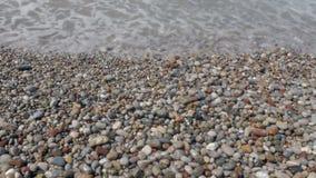 Взгляд сверху волн, пены и покрашенных камней каек пляжа видеоматериал