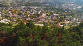 Взгляд сверху города в долине с холмами около съемки леса Граница зеленых леса и города в предгорьях холмов солнечно сток-видео