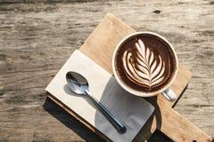 Взгляд сверху горячего искусства капучино кофейной чашки, ложки, ткани, прерывая доски на деревянном столе с космосом экземпляра Стоковое фото RF