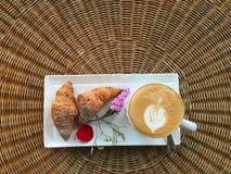 Взгляд сверху горячего кофе с круассанами украшает с цветком Стоковые Изображения