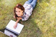 Взгляд сверху девушки студента работая на компьтер-книжке, лежа на траве в парке Стоковое Изображение RF
