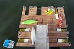Взгляд сверху деревянной пристани с пусковыми установками - каяки и затворы и спасательные жилеты разбросали вокруг и paddleboat  стоковые изображения rf