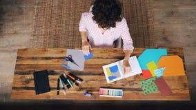Взгляд сверху дизайнера молодой дамы творческого работая в домашнем офисе делая коллаж от диаграмм вырезывания выплеск-бумаги и видеоматериал