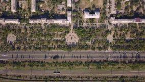 Взгляд сверху дороги мульти-майны с движением автомобилей, железной дорогой, парком, днем лета солнечным сток-видео