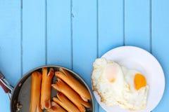 Взгляд сверху еды завтрака, зажаренных сосисок в черном лотке и яичниц в белом блюде на голубом деревянном столе, имеет космос эк Стоковая Фотография RF