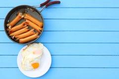 Взгляд сверху еды завтрака, зажаренных сосисок в черном лотке и яичниц в белом блюде на голубом деревянном столе Стоковая Фотография RF