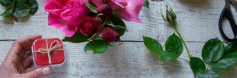 Взгляд сверху женского оформителя держа подарочную коробку, аранжируя розы на деревянном столе, концепции - fiorist, занятие, хоб стоковые изображения rf