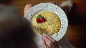 Взгляд сверху женщины вручает резать часть яичницы с ножом и вилкой Закройте вверх еды яичниц традиционно акции видеоматериалы