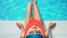 Взгляд сверху женщины в крышке и солнечных очках играя с водой около бассейна, каникул сток-видео