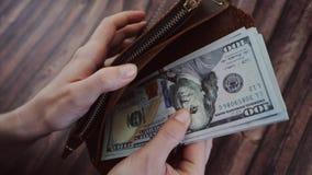 Взгляд сверху женщины подсчитывая и принимает вне доллары от ее коричневого кожаного бумажника Женщина держит портмоне против дер сток-видео