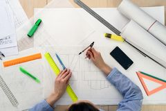 Взгляд сверху женщины ` s архитектора на работе на дизайне здания, на бумаге таблицы, правители, карандаши, компас, smartphone Стоковые Фотографии RF