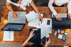 Взгляд сверху 3 женщин работая с документами используя компьтер-книжки сидя на столе Стоковая Фотография RF