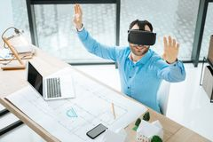 Взгляд сверху жизнерадостного архитектора испытывая шлемофон VR на работе Стоковое фото RF