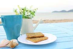 Взгляд сверху завтрака, голубой чашки горячего шоколада и хлеба шутихи на белом блюде на голубом виде на море деревянного стола Стоковые Фотографии RF
