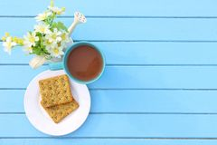 Взгляд сверху завтрака, голубой чашки горячего шоколада и хлеба шутихи на белом блюде на голубом деревянном столе с белым поддель Стоковая Фотография