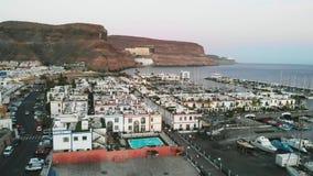 Взгляд сверху залива, гор и небольших домов на городе Puerto Mogan захода солнца, Канарских островах видеоматериал