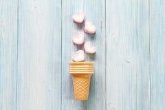 Взгляд сверху или плоское положение зефиров формы сердца и конуса мороженого на голубой деревянной предпосылке с космосом экземпл Стоковые Изображения RF