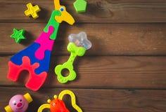 Взгляд сверху или плоское положение на красочных игрушках на темной деревянной предпосылке с космосом экземпляра стоковое изображение