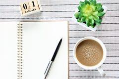 Взгляд сверху или плоское положение открытых бумаги тетради, календаря куба и кофейной чашки на предпосылке таблицы Стоковая Фотография