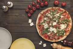 Взгляд сверху итальянской пиццы, tometoes вишни и пустых плит Стоковая Фотография