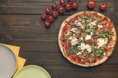 Взгляд сверху итальянской пиццы, tometoes вишни и пустых плит Стоковые Фотографии RF