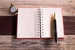 Взгляд сверху и теплый тон ручка кладя крышку пустой тетради красную и стоковое фото