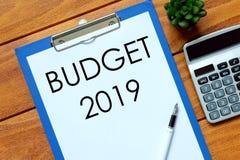 Взгляд сверху калькулятора, завода, ручки и бумаги написанных с бюджетом 2019 на деревянной предпосылке Дело, финансы и концепция стоковая фотография rf