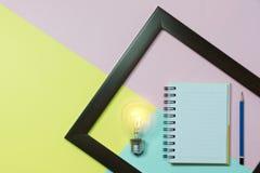 Взгляд сверху карандаша с электрической лампочкой и тетрадью на красочной задней части Стоковая Фотография