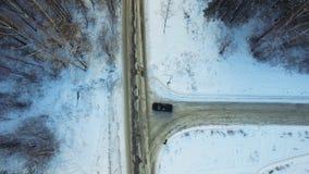 Взгляд сверху катания автомобиля в древесинах footage Автомобиль идет на дорогу зимы в древесинах Стоковая Фотография