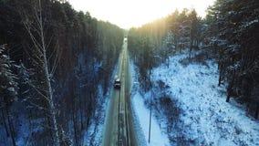 Взгляд сверху катания автомобиля в древесинах footage Автомобиль идет на дорогу зимы в древесинах Стоковые Фотографии RF