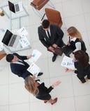 взгляд сверху команда дела обсуждая выходящ диаграммы вышед на рынок на рынок, стоя в офисе Стоковое фото RF