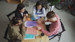 Взгляд сверху команды start-up дела мульти-этнической обсуждая новый проект в современном офисе просторной квартиры сток-видео