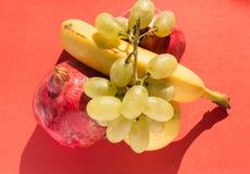 Взгляд сверху комплекта свежих фруктов: золотые яблоко, банан, гранатовое дерево и виноградины Стоковое Изображение RF