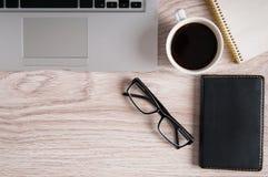Взгляд сверху компьтер-книжки и блокнота с стеклами и карманной книжкой на деревянных настольном компьютере и чашке кофе Стоковое Изображение