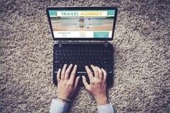 Взгляд сверху компьтер-книжки с вебсайтом бюро путешествий в экране, и женщине вручает искать Стоковое Изображение
