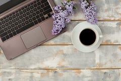 Взгляд сверху компьютера и чашки кофе и цветков сирени на бело-сером деревянном столе установьте текст Стоковое Фото