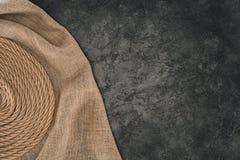 взгляд сверху коричневой морской веревочки аранжировало в круге на дерюге на темноте стоковые изображения