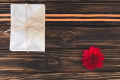 взгляд сверху коробки обернутое строкой, гвоздика и лента St. George на деревянных планках Стоковые Фотографии RF