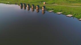 Взгляд сверху коттеджей близко к довольно озеру Остатки в сельской местности в сезоне лета 4K сток-видео