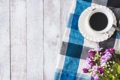 Взгляд сверху кофейной чашки с цветками и скатерть на предпосылке деревянного стола, открытом космосе для текста Стоковое Изображение RF