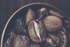 Взгляд сверху кофейных зерен внутри медной ложки на задней части нерезкости деревянной Стоковая Фотография RF