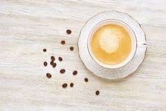 Взгляд сверху кофе капучино в яркой белой чашке на деревянном Стоковые Изображения RF
