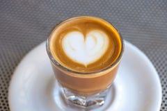 Взгляд сверху кофе cortado в стекле с пеной в форме сердца Стоковая Фотография
