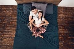 Взгляд сверху Красивый молодой человек обнимая беременную женщину сидя близко к одину другого на кровати стоковая фотография rf