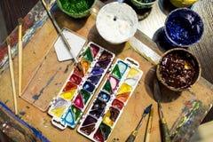 взгляд сверху красок плаката и красок акварели на деревянном столе Стоковые Изображения