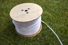 Взгляд сверху крена белого промышленного электрического кабеля на большом деревянном вьюрке изолированном outdoors на зеленой тра стоковые изображения rf