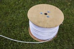 Взгляд сверху крена белого промышленного электрического кабеля на большом деревянном вьюрке изолированном outdoors на зеленой тра стоковые фото