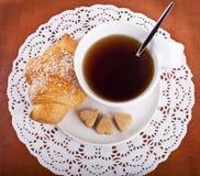 Взгляд сверху круасанта и чашек чаю или кофе Стоковое Фото