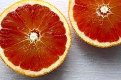 Взгляд сверху крупного плана апельсина половинной крови на белой затрапезной смотря таблице Стоковое Изображение RF