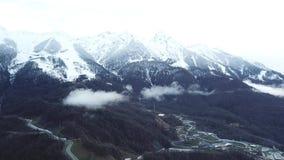 Взгляд сверху курорта около гор со снежными пиками Небольшой лыжный курорт на ноге горы со снежными пиками в тумане внутри сток-видео